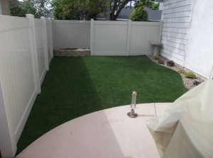 Artificial grass lawn by FieldTurf on side yard of residential home. Durable, looks real, and feels real. The perfect solution.