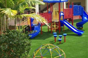 Childrens FieldTurf grass around kids playground equipment. Clean and Safe Fun.