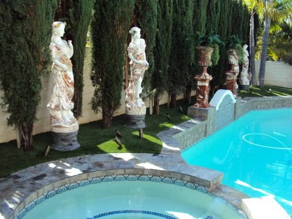 FieldTurf Grass surrounding Pool Area with Statues and Lighting. Durable, looks real, feels real and clean with no maintenance.