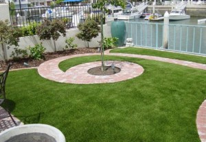 Waterfront residential backyard with FieldTurf artificial lawn. No fading and immune to salt spray and pool chemicals. The perfect solution.